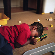 A boy crashes with his toy trains.
