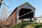 "Cox Ford Covered Bridge was built in 1913 in Burr Arch style by J.A. Britton over Sugar Creek. Turkey Run State Park, in historic Parke County, Indiana, USA. The traditional ""Cross this bridge at a walk"" sign requires slow vehicle speed. A roof and red painted wood sides protect the historic bridge."