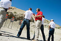Instructor assisting people aiming guns at firing range