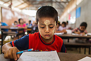 06 MARCH 2014 - MAE SOT, TAK, THAILAND: A boys works on his final exam for the semester at the Sky Blue School. There are approximately 140 students in the Sky Blue School, north of Mae Sot. The school is next to the main landfill for Mae Sot and serves the children of the people who work in the landfill. The school relies on grants and donations from Non Governmental Organizations (NGOs). Reforms in Myanmar have alllowed NGOs to operate in Myanmar, as a result many NGOs are shifting resources to operations in Myanmar, leaving Burmese migrants and refugees in Thailand vulnerable. The Sky Blue School was not able to pay its teachers for three months during the current school year because money promised by a NGO wasn't delivered when the NGO started to support schools in Burma. The school got an emergency grant from the Burma Migrant Teachers' Association and has since been able to pay the teachers.      PHOTO BY JACK KURTZ