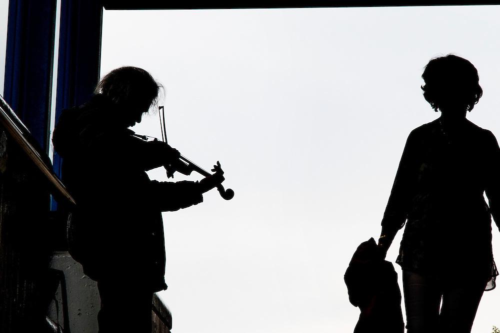 Nederland, Amsterdam, 13 juni 2016<br /> Vioolspeler bij de ingang van de metro. <br /> Straatmuzikant probeert een paar euro te verdienen.<br /> <br /> Foto: (c) Michiel Wijnbergh