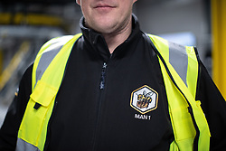 "© Licensed to London News Pictures . 04/12/2019. Manchester , UK . Manchester bee branded delivery badges on the floor inside the ""MAN1"" Amazon fulfilment centre warehouse at Manchester Airport in the North West of England . Photo credit : Joel Goodman/LNP"