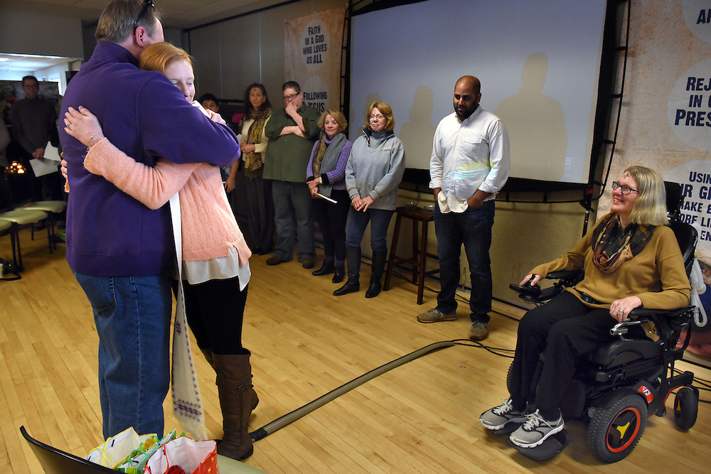 Mara Lavitt -- Special to the Hartford Courant<br /> February 14, 2016, Glastonbury<br /> Amyotrophic Lateral Sclerosis (ALS) forced Nancy Butler of Marlborough, right, to step down as pastor of the Riverfront Family Church in Glastonbury during the Sunday service. Three co-pastors will take over for her including her daughter Liza Arulampalam of Hartford, center, who just received a stole from her father Greg Butler, left. The stole belonged to Nancy who received it from a mentor.