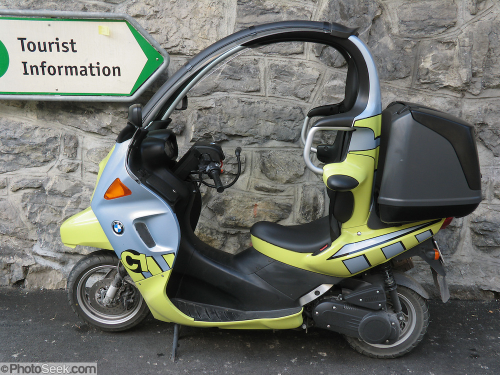 "A ""Tourist Information"" sign in Switzerland, Europe, points towards a BMW C1 enclosed scooter, made by Bertone for BMW and sold for a limited time 2000-2001. Roll bars, safety belts, and other design features were meant to eliminate need for a helmet, which conflicted with unamended helmet laws in UK and Sweden. Other countries considered wearing a helmet with a safety belt to risk neck injuries. High center of gravity made travel at slow speeds harder to learn than for motorcycles."