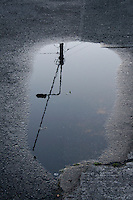 Streetlight reflected in puddle on pavement after the rain in Dublin Ireland