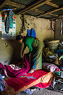 Kalpana Tamang (40), folds the winter blanket that was provided to her in the earthquake relief 'Home-in-a-Box' tin trunk by SOS Childrens Villages in her temporary shelter in Kavre, Bagmati, Nepal on 30 June 2015.  Kalpana, a widow with 3 children, has been supported by SOS Children's Villages for many years now and had receive the Home-in-a-Box after the earthquake destroyed her house, almost killing her two daughters. She now lives in a temporary shelter, sharing her dwelling with farm animals, and is trying to make ends meet by weaving bamboo baskets to supplement the financial assistance provided by SOS Childrens Villages. The NGO mostly supports her children's welfare and schooling as well as provides her with essential household and schooling items like kitchen utensils and school books and uniforms. Photo by Suzanne Lee for SOS Children's Villages