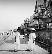 Two young women walk along a promenade by a beach in France, during summer. Circa 1900