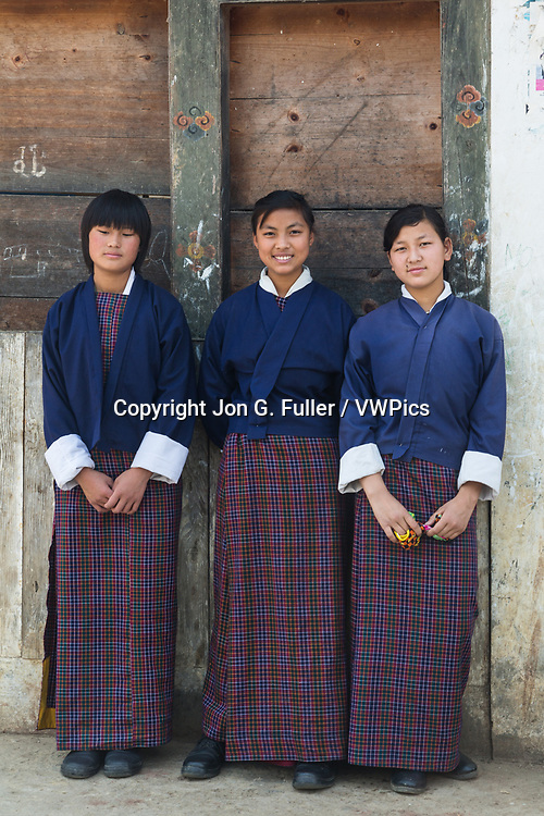 Three young girls in school uniforms of the traditional kira skirt and tego jacket.   Punakha, Bhutan.