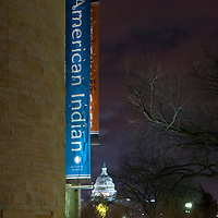 Exterior sign at the National Museum of the American Indian in Washington, DC with the U.S. Capitol in the background.