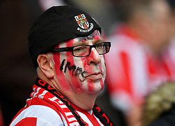 A Lincoln City fan in the stand wearing face paint