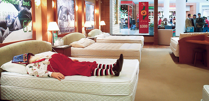 Santa takes an afternoon nap at Select Comfort while bystanders take a peak at him from the store front inside Apache Mall. He generally takes a nap everyday on his break using ear plugs and a cover for his eyes.  Children have been  known to watch him sleep while others like to wake him up.