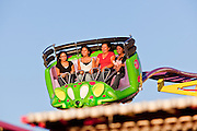 "Oct. 21, 2009 -- PHOENIX, AZ: People ride the ""Crazy Coaster"" on the midway at the Arizona State Fair in Phoenix, AZ. The fair runs through November 8.   Photo by Jack Kurtz"