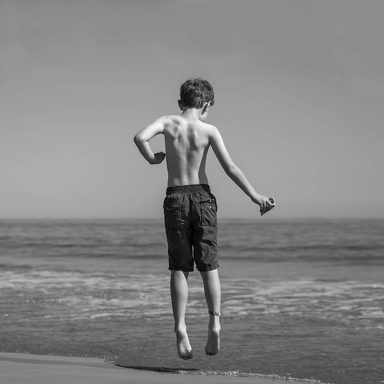 Photograph of boy jumping above waves on Hull beach. Hull MA