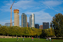 North America, United States, Washington, Bellevue. People playing games in Downtown Park in the autumn. Skyline and construction cranes in background.