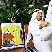 Reading his newspaper to pass the time, a businessman in traditional Gulf state thawb and agal headdress awaits his flight from Bahrain in the Persian Gulf. With a plastic bag alongside containing Duty Free purchases and with the cheeky face for the Adams kids clothing brand for his young family, the man studies the latest news from the Gulf states and further Middle-East region before boarding his airline departure, seen here months before the terrorist attacks on America that changed the public's attitude to flying on commercial airliners.