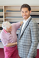Senior tailor measuring young customer for making suit