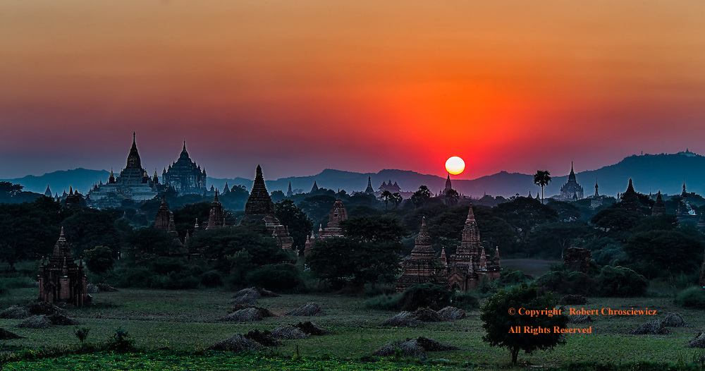 Another hot and dry day draws to a close with a fiery sunset, the sun about to hide away behind the nearby hills of Bagan Myanmar.<br />
