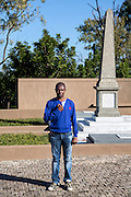 """Mandla Nxumalo, 42, pictured beside the grave of John Dube at the Ohlange High School, in Inanda, South Africa. John Dube was the founding president of the South African Native National Congress (SANNC), which became the African National Congress in 1923. After casting his vote in 1994, Nelson Mandela visited the grave and said, """"Mr President, I have come to report to you that South Africa is now free."""""""