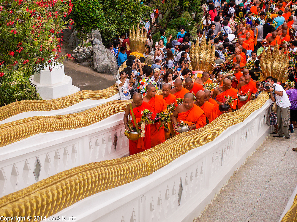 "12 JULY 2014 - PHRA PHUTTHABAT, SARABURI, THAILAND: Buddhist monks climb the stairs to Wat Phra Phuttabat during the Tak Bat Dok Mai in Saraburi province of Thailand. Wat Phra Phutthabat is famous for the way it marks the beginning of Vassa, the three-month annual retreat observed by Theravada monks and nuns. The temple is highly revered in Thailand because it houses a footstep of the Buddha. On the first day of Vassa (or Buddhist Lent) people come to the temple to ""make merit"" and present the monks there with dancing lady ginger flowers, which only bloom in the weeks leading up Vassa. They also present monks with candles and wash their feet. During Vassa, monks and nuns remain inside monasteries and temple grounds, devoting their time to intensive meditation and study. Laypeople support the monks by bringing food, candles and other offerings to temples. Laypeople also often observe Vassa by giving up something, such as smoking or eating meat. For this reason, westerners sometimes call Vassa ""Buddhist Lent.""    PHOTO BY JACK KURTZ"