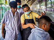 12 SEPTEMBER 2018 - BANGKOK, THAILAND: A barber instructor (center, yellow shirt) works with students giving a traveler a haircut at Hua Lamphong train station in Bangkok. Barber schools set up in the station and offer free haircuts to travelers.    PHOTO BY JACK KURTZ