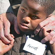July 13, 2006 - Six-year-old Arriet, who is HIV positive, healthy, and on ARV's, rests her head on President Clinton's hand as he visits the antiretroviral treatment center, Karabong Clinic, at Mafeteng Hospital in Lesotho. Arriet was among the first group of children to receive ARV treatment donated by the Clinton Foundation in 2004. Phto by Evelyn Hockstein