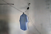 A shirt hang from an electric cable in a  makeshift  house in Bab Al Aziziya. Hundreds of families displaced by the war and not more able to pay a rent found shelter in the buildings not completely demolished in Bab Al Aziziya, the Kaddafi stronghold and symbol of the regime in center Tripoli.