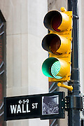 Green traffic light for GO on Wall Street in New York, USA