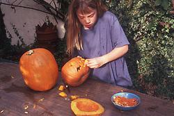 Girl cutting up pumpkin for Halloween,