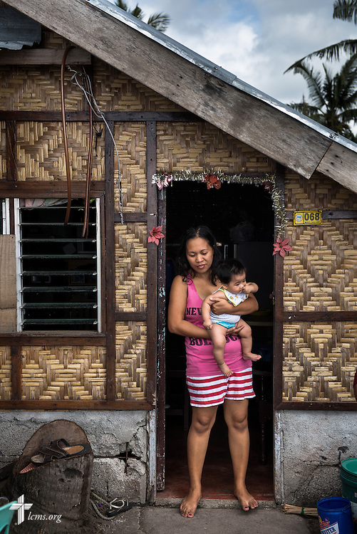 A woman and her child stand in the doorway of their newly rebuilt home in Balugo, Leyte Province, Philippines, on Saturday, March 15, 2014. Her home was damaged in Typhoon Haiyan, and repaired with the help of LCMS disaster dollars.  LCMS Communications/Erik M. Lunsford