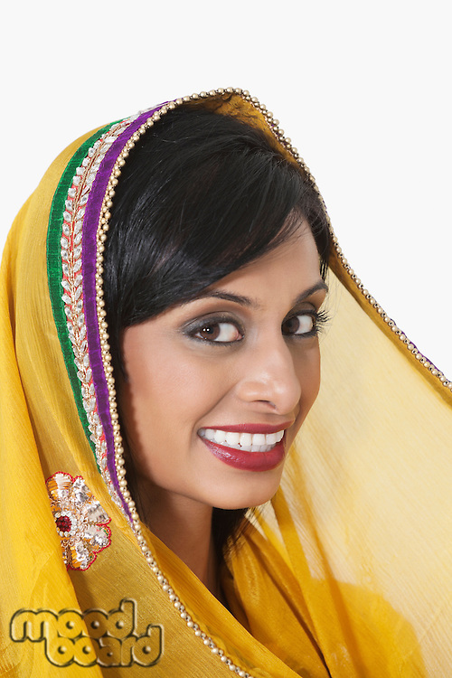 Close-up portrait of Indian woman with yellow dupatta over gray background