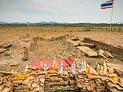 02 APRIL 2016 - NA SAK, LAMPANG, THAILAND:  The ruins of the Buddhist temple in Sobjant village. The soft drinks were left as offerings by people who visited the temple. The village of Sobjant in Na Sak district in Lampang province was submerged when the Mae Chang Reservoir was created in the 1980s. The village was relocated to higher ground a few kilometers from its original site. The drought gripping Thailand drained the reservoir and the foundations of the Buddhist temple in the original village became visible early in 2016. Thai families come down to the original village to pray in the ruins of the temple and look at what's left of the village. This is the first time in more than 30 years that this area has not been under two meters of water.     PHOTO BY JACK KURTZ