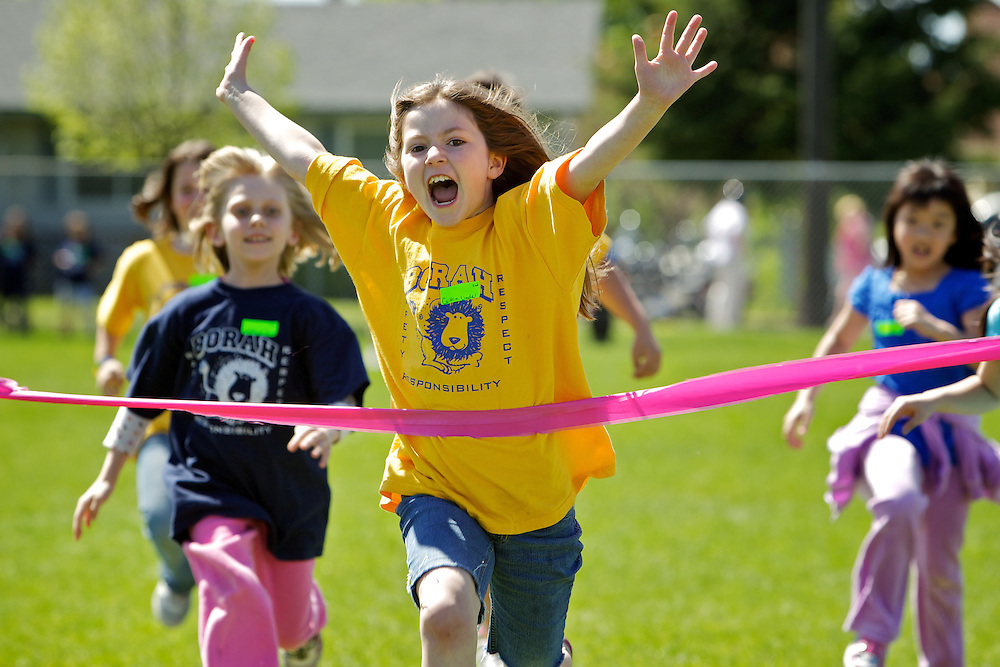 Caitlyn Lindell, 8, celebrates her first place finish as she crosses the tape in the second grade 50-yard dash during Borah Elementary's track and field event Thursday.