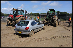 Cars stuck in the mud at one of the car parks at the Isle of Wight Festival after heavy rainfall, Sunday June 24, 2012. Photo By i-Images