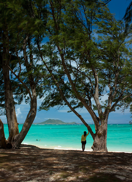Girl and trees silhouetted againt the aqua blue water at Kailua Beach park, Oahu, Hawaii