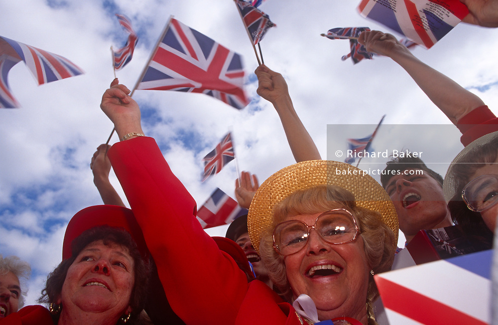 Patriotic Londoners sing wartime songs during 1995 VE Day 50th anniversary celebrations in London. Looking up at the Britons who are singing the words of the national anthem, they wave their small union jack flags in the summer air. In the week near the anniversary date of May 8, 1945, when the World War II Allies formally accepted the unconditional surrender of the armed forces of Germany and peace was announced to tumultuous crowds across European cities, the British still go out of their way to honour those sacrificed and the realisation that peace was once again achieved. Street parties now – as they did in 1945 – played a large part in the country's patriotic well-being.
