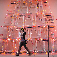 A woman walks past the 'Edgemar Holiday Tree' on Main street on Sunday, November 21, 2010. The holiday tree is constructed from 25 shopping carts by Artist Anthony Schmitt.