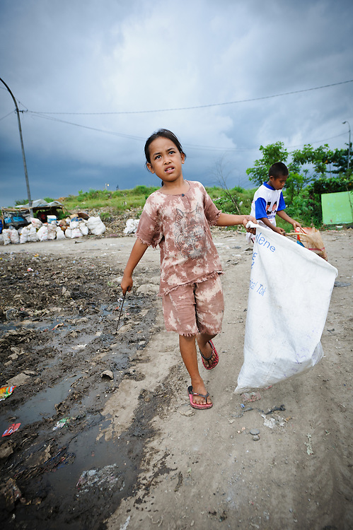 Idris, 13, and Annie, 8, returning home with sacks of recycled waste at the 'Trash mountain', Makassar, Sulawesi, Indonesia.