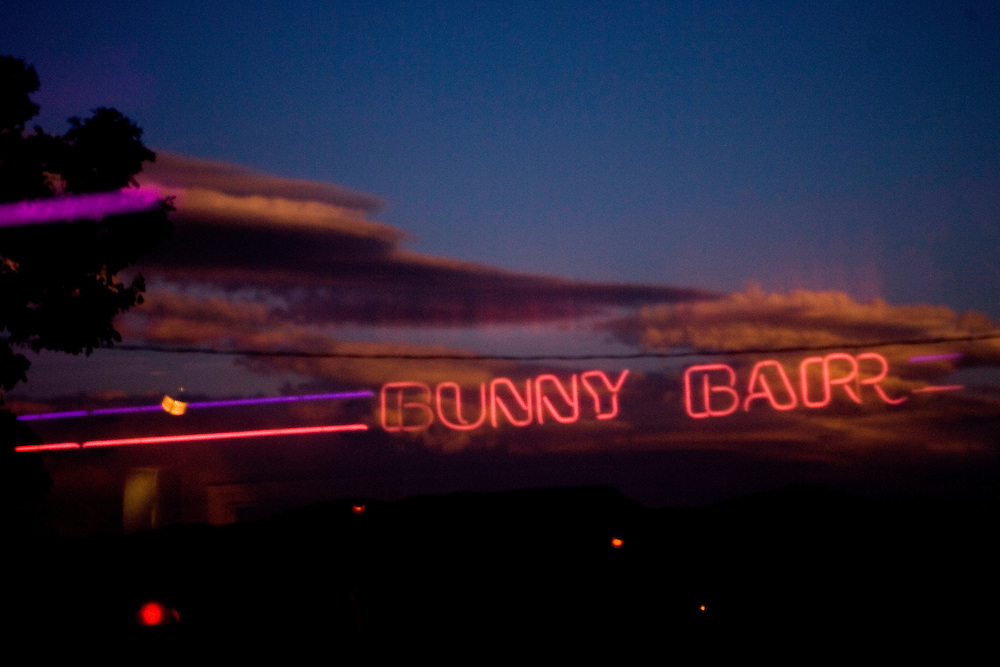 """A neon sign is reflected in the glass door of the Moonlite Bunny Ranch brothel in Mound House, NV on Friday, July 28, 2006...The Moonlite Bunny Ranch brothel in Mound House, Nevada - just a few miles from the state capital in Carson City - first opened in 1955. The Ranch is a legal, licensed brothel owned by Dennis Hof. It's featured in the HBO series """"Cathouse."""""""