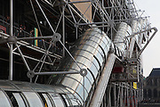 Low angle view of exterior escalator in tube, Centre Georges Pompidou, 1971-77, Paris, France. Centre Georges Pompidou, or  Pompidou Centre, is an arts complex in the Beaubourg area of the 4th arrondissement of Paris. The Centre was designed in high tech style by the Italian architect Renzo Piano, the British architect couple Richard Rogers and Su Rogers, Gianfranco Franchini, the British structural engineer Edmund Happold and Irish structural engineer Peter Rice to whom the project was awarded in 1971 after a design competition. Picture  by Manuel Cohen.