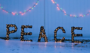 Colorful holiday lights outline the word PEACE on an cold and icy winter evening