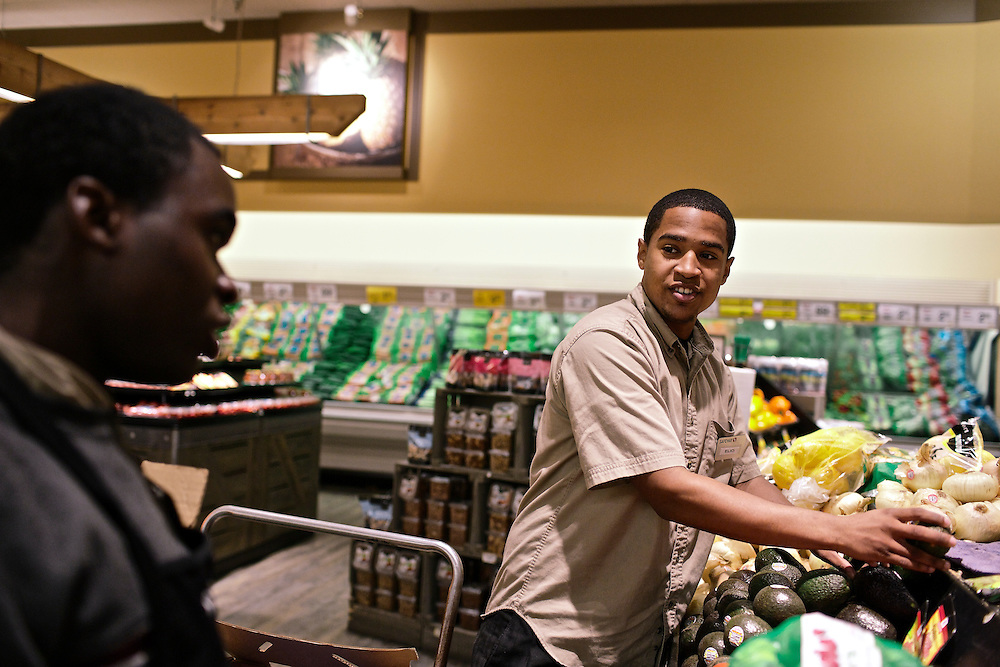 Elio Perdomo, right, talks with co-worker Geobort Amtoung, left, as Perdomo restocks shelves in the produce section at a Safeway grocery store in Silver Sping, MD. Perdomo, a student at Montgomery College, tries to take classes in the morning and works up to 16 hours a week at the supermarket.