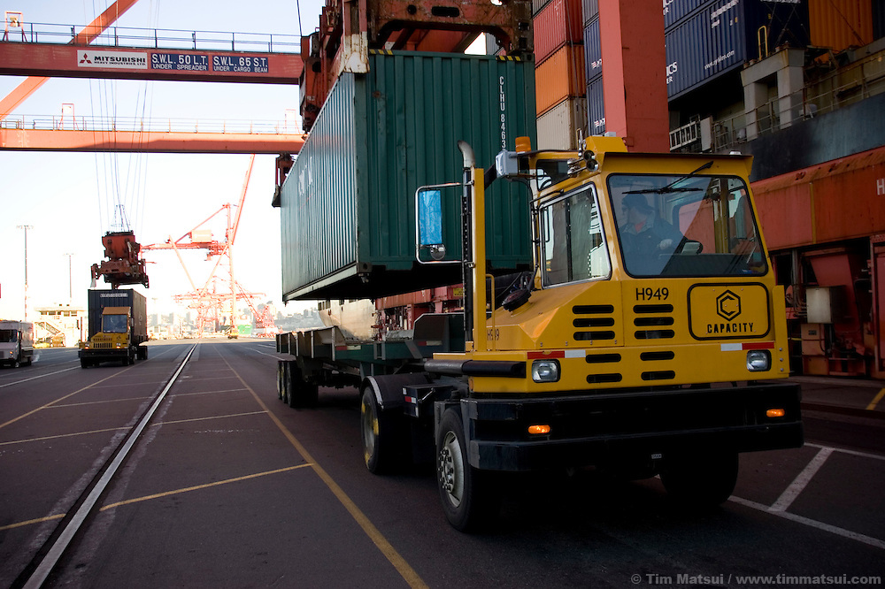 A container is loaded onto an SSA Marine tractor trailer, called a hustler, after being offloaded from a cargo ship by a ship-to-shore crane at Terminal 18 at the Port of Seattle. The diesel fueled hustler will soon be running biodiesel, a more environmentally friendly alternative fuel produced from oilseed crops.