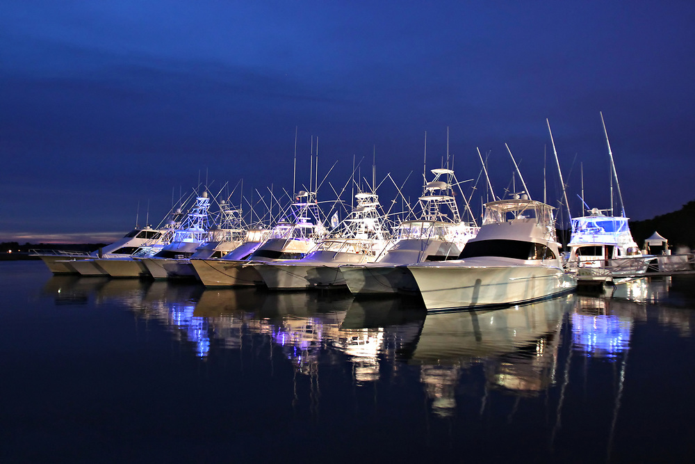Illuminated sport fishing yachts docked in marina ready for sport fishing offshore