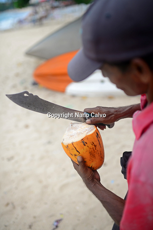 Coconut seller cuts the coconut on Unawatuna beach, Sri Lanka