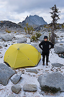 A woman standing a smiling outside her tent in the Enchantment Lakes Wilderness Area, Washington Cascades, USA.
