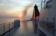 ships smokestack bellowing black smoke at sunset