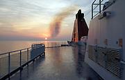 ships smokestack bellowing black smoke at sunset