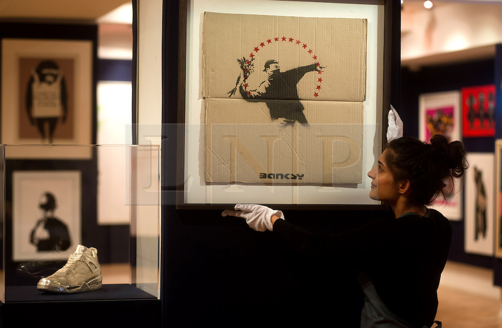 © Licensed to London News Pictures. 12/04/2013. London, UK. Gallery assistant hangs  Banksy's Flower Chucker during the preview for Climbing The Walls With Banksy at Bonham's Urban Art Sale at Bonham's auction house in London, April 12, 2013. Photo credit : Peter Kollanyi/LNP