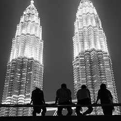 People silhouetted against the glow of the Petronas Towers in Kuala Lumpur, Malaysia.