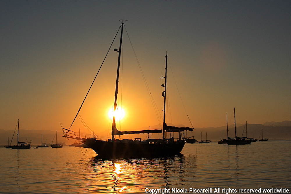 The anchored Sail boats in the  Bay of Banderas of the La Cruz de Huana Caxtle coast Mexico are awaked by a beautiful golden sunshine.